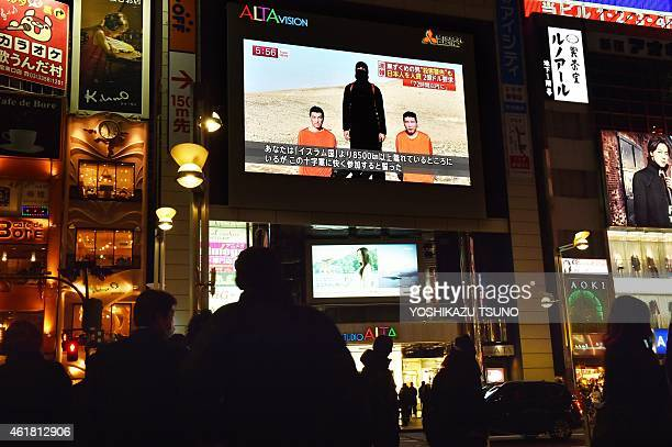 People look at a large TV screen in Tokyo on January 20 2015 showing news reports about two Japanese men who have been kidnapped by the Islamic State...