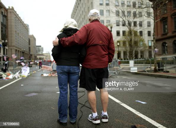 People look at a makeshift memorial on Boylston Street April 20 near scene of Boston Marathon explosions as people get back to the normal life the...