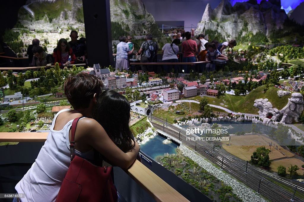 People look at a miniature world inside the first Mini World park in France in Vaulx-en-Velin near Lyon, on June 30, 2016 / AFP / PHILIPPE