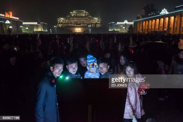 TOPSHOT People look at a noticeboard after a fireworks display in front of Kim IlSung square as they visit an ice festival near the Taedong river on...