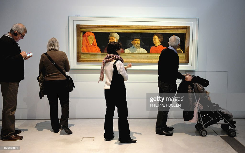 People look at a paint 'five founders of the Florentin art' at the Louvre-Lens museum on December 31, 2012 in Lens, northern France. Three weeks after its inauguration, the museum welcomed its 100.000th visitor on December 28, 2012.