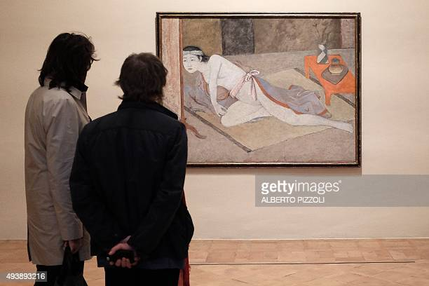 People look at a painting by late French artist Balthus as he visits the exhibition dedicated to his work at the Villa Medici in Rome on October 23...
