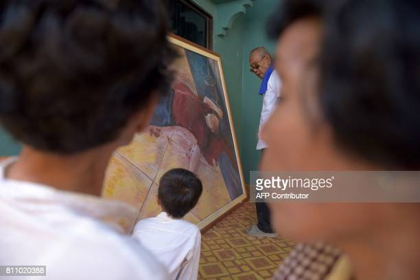 People look at a painting depicting the murder scene of the Cambodian critic Kem Ley during the first anniversary of his murder at his mother's home...