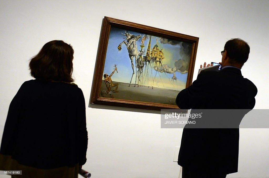 People look at a painting entitled 'The Temptation of St.Anthony' (1946) by Spanish surrealist artist Salvador Dali during the exhibition 'Dali. All of the poetic suggestions and all of the plastic possibilities' at the Reina Sofia museum in Madrid on April 25, 2013.
