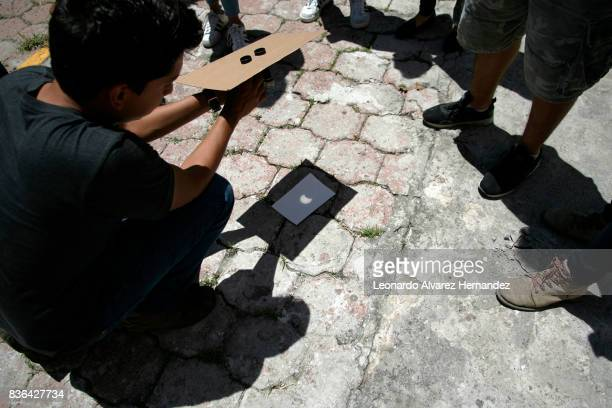 People look at a partial solar eclipse in the Institute of Astronomy and Meteorology at Guadalajara University on August 21 2017 in Guadalajara México
