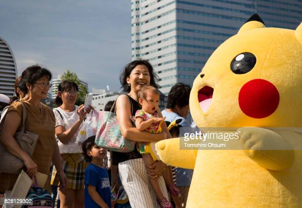 People look at a performer dressed as Pikachu a character from Pokemon series game titles during the Pikachu Outbreak event hosted by The Pokemon Co...