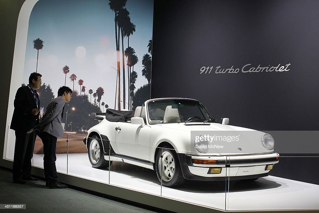People look at a Porsche 911 Turbo Cabriolet is displayed during media preview days at the 2013 Los Angeles Auto Show on November 20, 2013 in Los Angeles, California. The LA Auto Show was founded in 1907 and is one of the largest with more than 20 world debuts expected. The show will be open to the public November 22 through December 1.