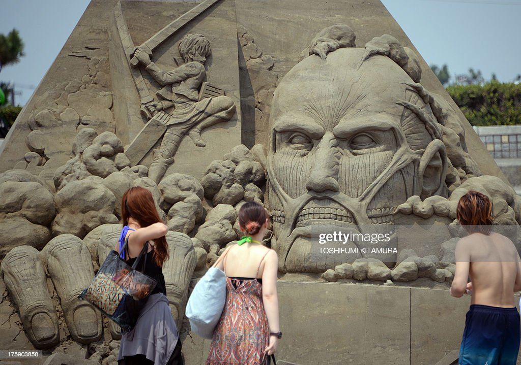 People look at a sand sculpture featuring 'Attack on Titan' at Enoshima east beach in Fujisawa, Kanagawa prefecture, some 50 kilometres southwest of Tokyo on August 10, 2013. A week-long exhibition of the sand art, a Japanese manga series by Hajime Isayama, started on August 9 to mark the sales of 23 million copies in Japan.