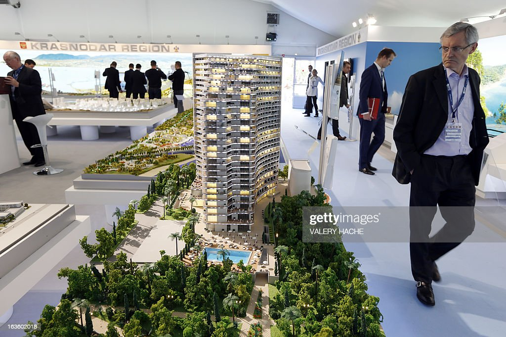 People look at a scale model of 'Karat Apartments' on the Russian Federation stand on March 13, 2013 at the Palais des Festivals in Cannes, southeastern France, during the MIPIM, an international real estate show for professionals. The event takes place until March 15.