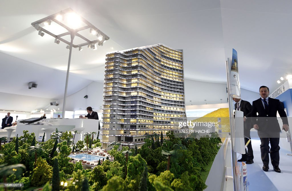People look at a scale model of 'Karat Apartments' on the Russian Federation stand on March 13, 2013 at the Palais des Festivals in Cannes, southeastern France, during the MIPIM, an international real estate show for professionals. The event takes place until March 15. AFP PHOTO / VALERY HACHE