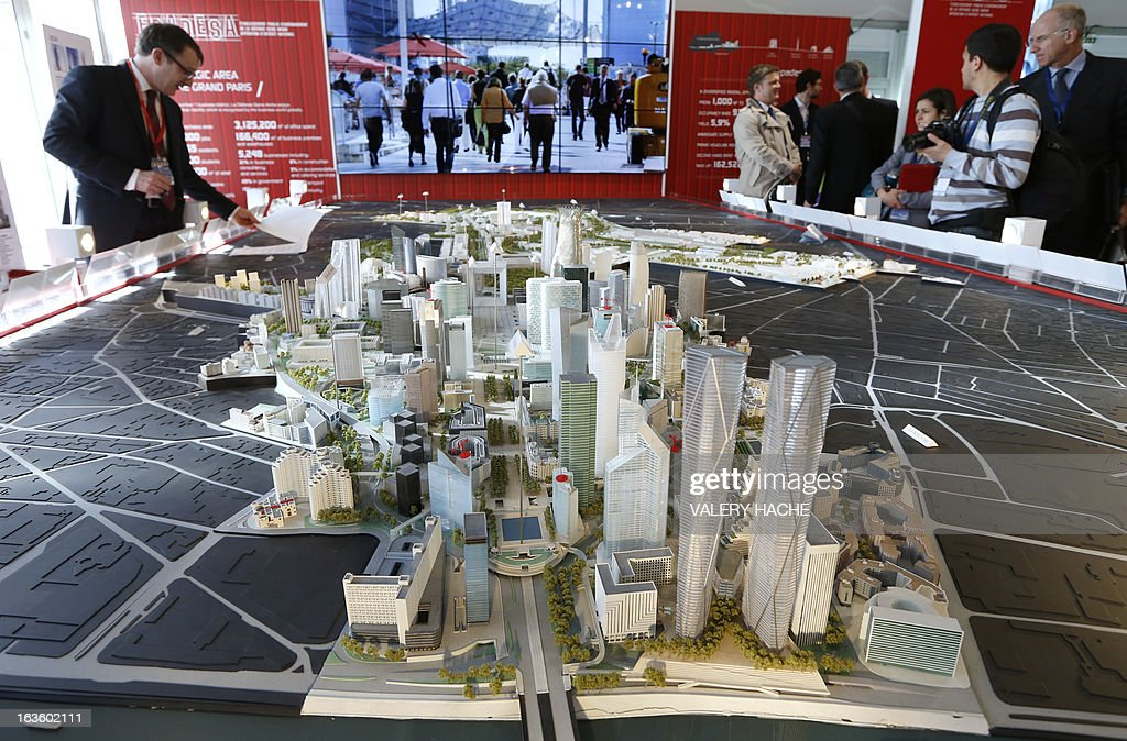 People look at a scale model of the French 'La Defense Seine Arche' business district on March 13, 2013 at the Palais des Festivals in Cannes, southeastern France, during the MIPIM, an international real estate show for professionals. The event takes place until March 15. AFP PHOTO / VALERY HACHE