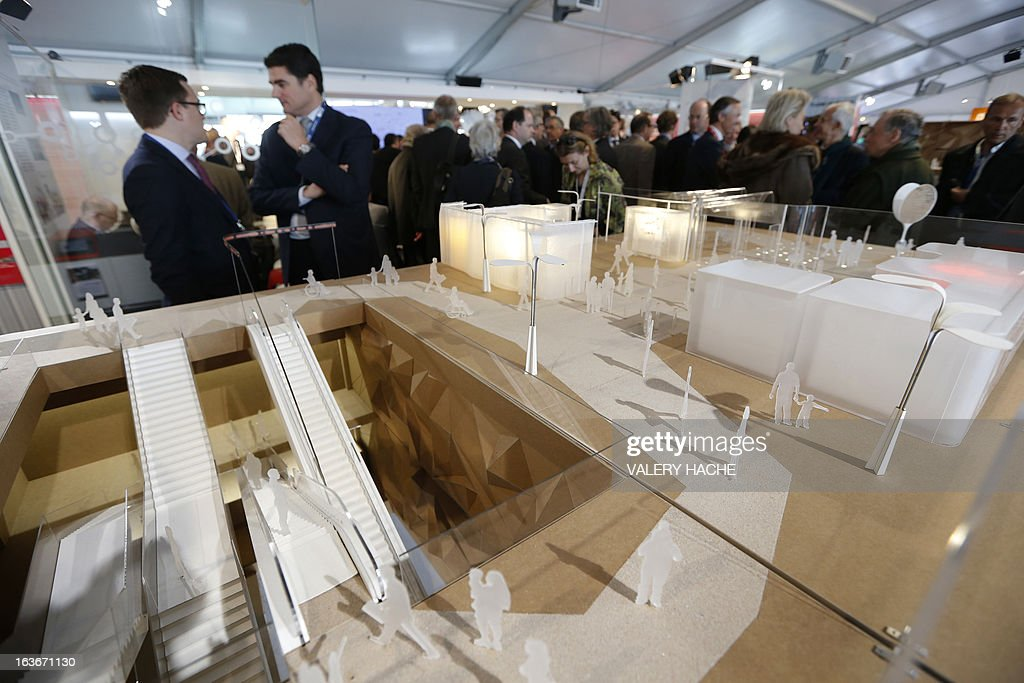 People look at a scale model of the 'Gares du Grand Paris' project at the Palais des Festivals on March 14, 2013 in Cannes, southeastern France, where takes place the MIPIM, an international real estate show for professionals. The event takes place until March 15.