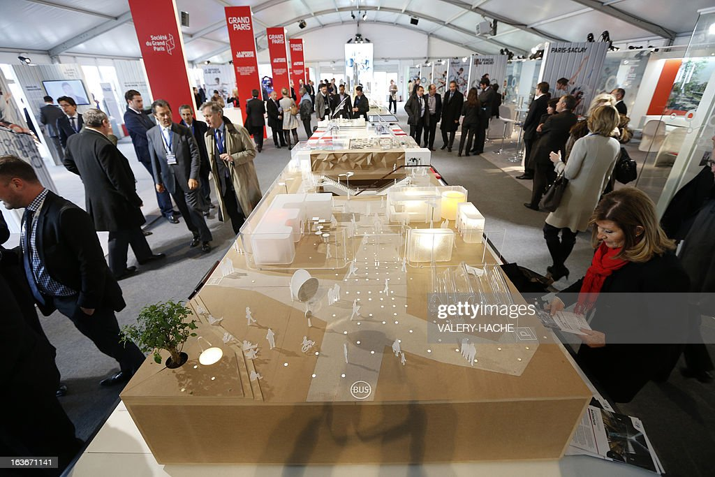 People look at a scale model of the 'Gares du Grand Paris' project on March 14, 2013 at the Palais des Festivals in Cannes, southeastern France, where takes place the MIPIM, an international real estate show for professionals. The event takes place until March 15.