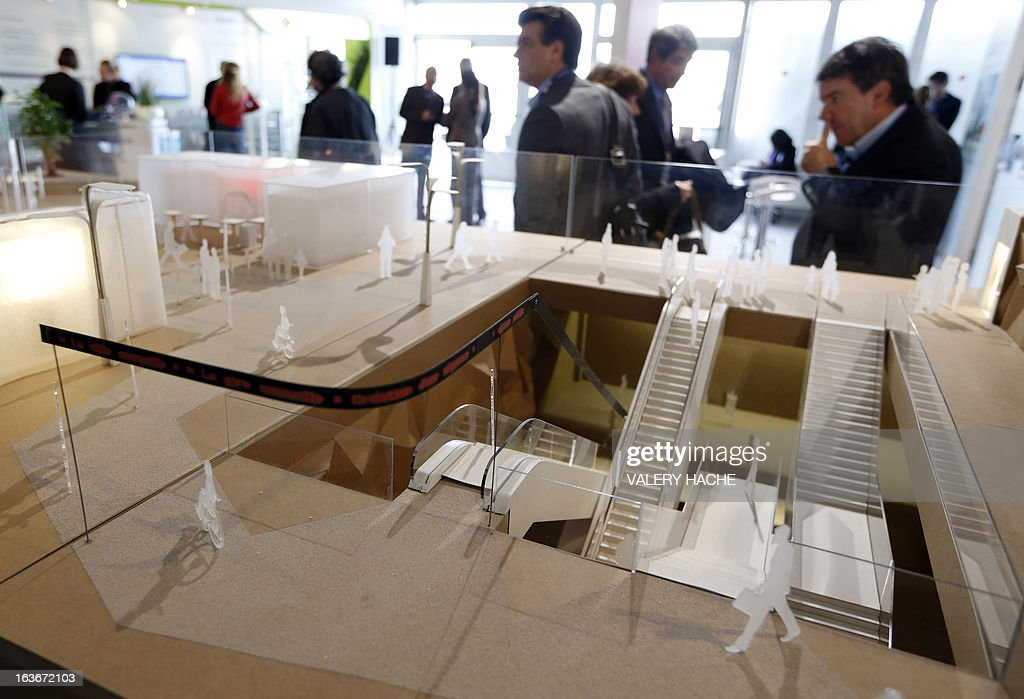 People look at a scale model of the 'Gares du Grand Paris' project on March 14, 2013 at the Palais des Festivals in Cannes, southeastern France, where takes place the MIPIM, an international real estate show for professionals. The event takes place until March 15. AFP PHOTO / VALERY HACHE