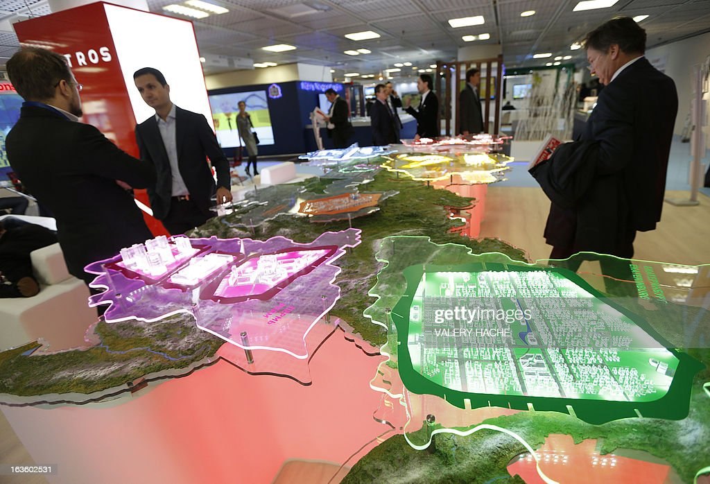 People look at a scale model of the 'Kortros' project on March 13, 2013 at the Palais des Festivals in Cannes, southeastern France, during the MIPIM, an international real estate show for professionals. The event takes place until March 15.