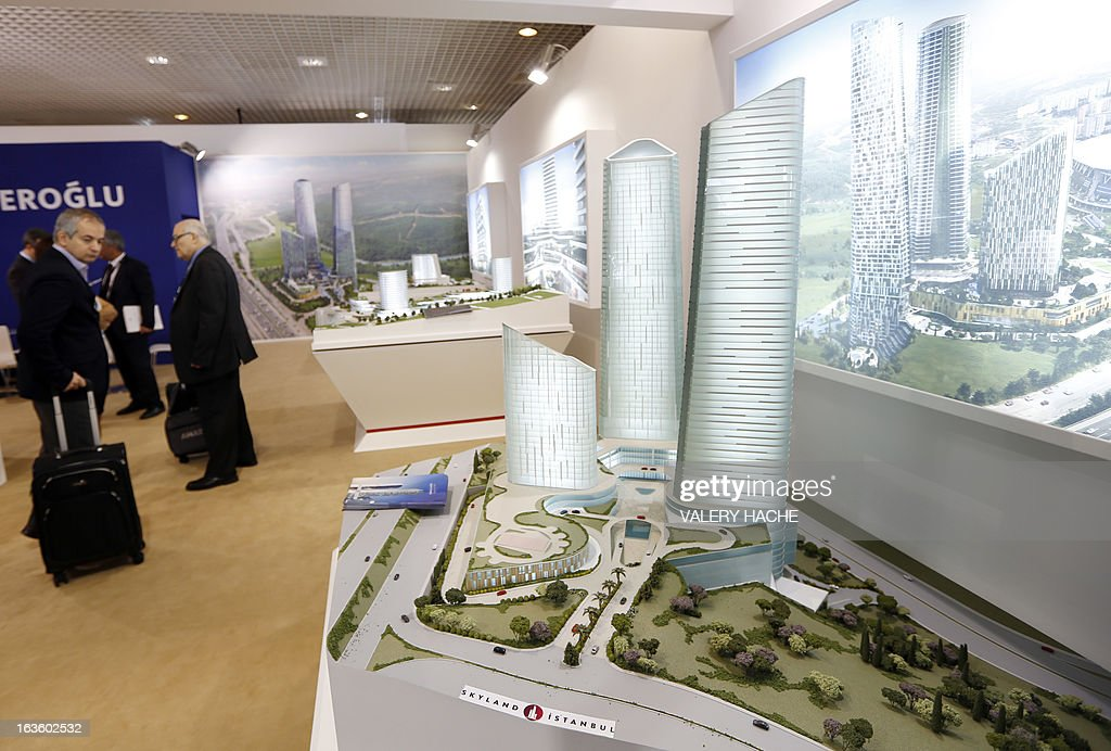 People look at a scale model of the 'Skyland Istanbul' district on March 13, 2013 at the Palais des Festivals in Cannes, southeastern France, during the MIPIM, an international real estate show for professionals. The event takes place until March 15. AFP PHOTO / VALERY HACHE