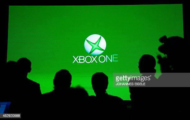 People look at a screen which shows the Xbox One logo during the presentation of the Xbox One in Shanghai on July 30 2014 The Xbox One will launch in...