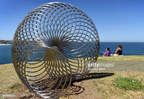 People look at a sculpture by artist George Andric of Australia titled 'sisyphus' overlooking Sydney's coastline as artists from 16 countries prepare...