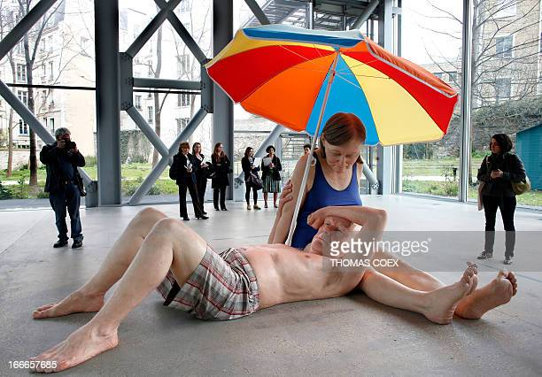 People look at a sculpture by Australian artist Ron Mueck exhibited at the Fondation Cartier on April 15 2013 in Paris AFP PHOTO THOMAS COEX