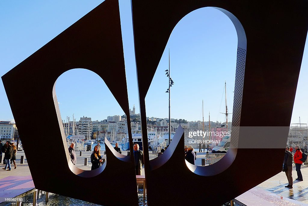 People look at a sculpture shaped as a 'M' (for Marseille) displayed in the middle of a fountain, designed by local set designer Philippe Malta, on January 11, 2013 in Marseille, southern France, as one of a number of exhibitions opening in Marseille in relation to the city being named 2013 European 'Capital of Culture'. On January 12, the city will be named 'Capital of Culture' which will kick off a range of exhibitions and events.