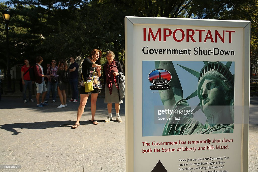 People look at a sign for informing that the Statue of Liberty is closed due to the government shutdown in Battery Park on October 1, 2013 in New York City. Federal museums and parks across the nation are closed starting today due to a government shutdown for the first time in nearly two decades. The Dow Jones industrial average, the S&P 500 and the Nasdaq all rose slightly higher in early trading Tuesday morning.