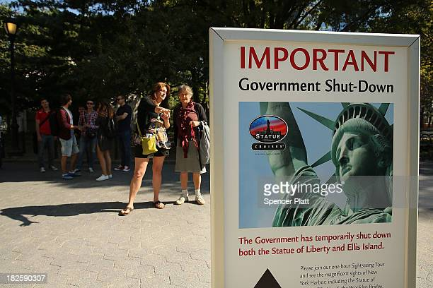 People look at a sign for informing that the Statue of Liberty is closed due to the government shutdown in Battery Park on October 1 2013 in New York...