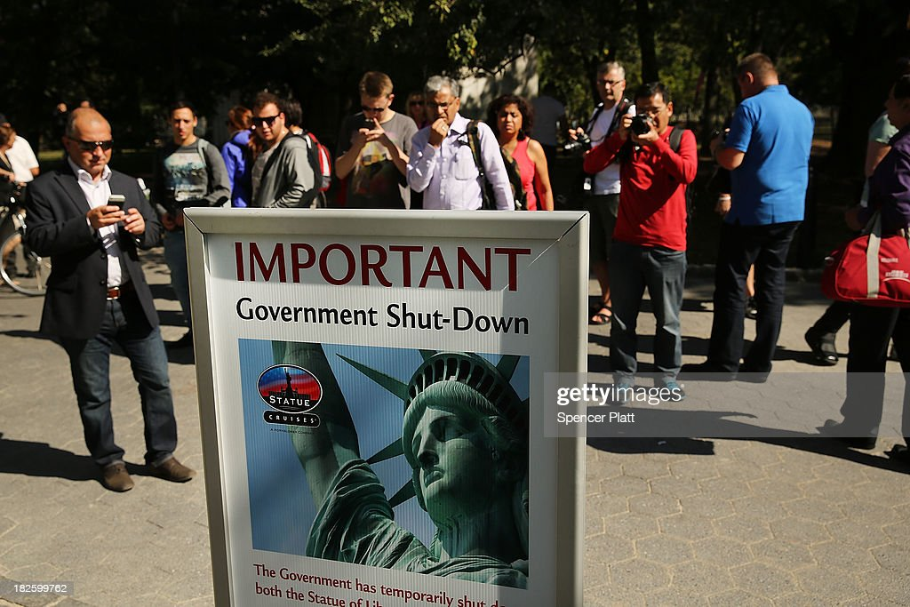 People look at a sign informing them that the Statue of Liberty is closed due to the government shutdown in Battery Park on October 1, 2013 in New York City. Federal museums and parks across the nation are closed starting today due to a government shutdown for the first time in nearly two decades. The Dow Jones industrial average, the S&P 500 and the Nasdaq all rose slightly higher in early trading Tuesday morning.