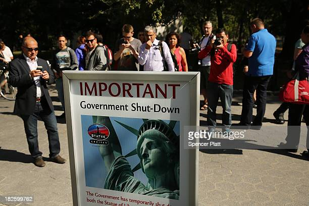 People look at a sign informing them that the Statue of Liberty is closed due to the government shutdown in Battery Park on October 1 2013 in New...