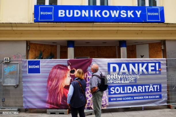 People look at a sign reading 'Thanks for you solidarity we are soon back for you' fixed at a fence in front of the Budnikowsky shop after it has...