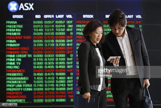 People look at a smartphone in front of electronic boards displaying stock information inside the Australian Securities Exchange operated by ASX Ltd...