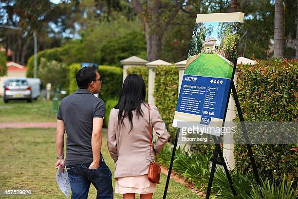 People look at a Smyth Estate Agents auction sign on display outside a house in the suburb of Beacon Hill in Sydney Australia on Saturday Oct 18 2014...