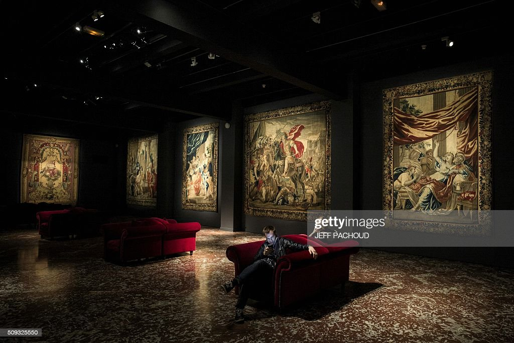People look at a tapistry during their visit the Musee des Tissus (Museum of Textiles) in Lyon on February 9, 2016. / AFP / JEFF PACHOUD