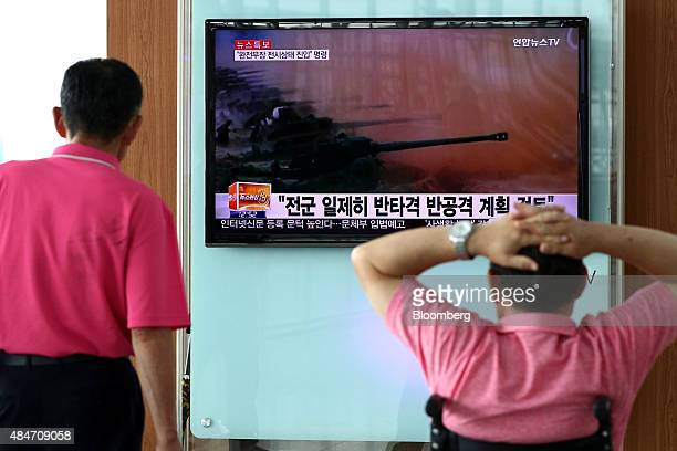 People look at a television screen showing a news broadcast on North Korea's exchange of fire with South Korea at Seoul Station in Seoul South Korea...