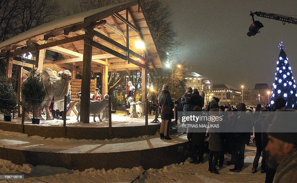 People look at a traditional religious Nativity scene in a crib in front of the Roman Catholic Cathedral of Vilnius on December 24, 2012.