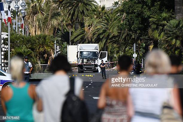 TOPSHOT People look at a truck stand guarded by the police on the Promenade des Anglais seafront in the French Riviera town of Nice on July 15 hours...