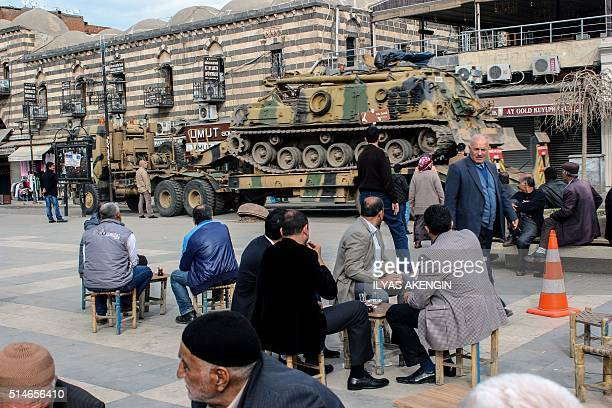 People look at a Turkish army Tank transported by a truck on March 10 2016 in the historical Sur district of Diyarbakir Residents of Cizre in...