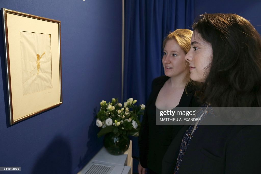 People look at a watercolor by Antoine de Saint-Exupery featuring Le Petit Prince (1942) on May 27, 2016 in Paris. The art work will be auctioned on May 31. / AFP / MATTHIEU