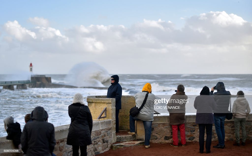 People look at a wave breaking against a pier and a lighthouse in Les Sables-d'Olonne, western France, on February 9, 2016. High winds buffeted northwestern Europe on February 8, leaving one woman in France in a coma after she was hit by an advertising hoarding. Electricity was cut to 5,000 homes in northern France. / AFP / LOIC VENANCE