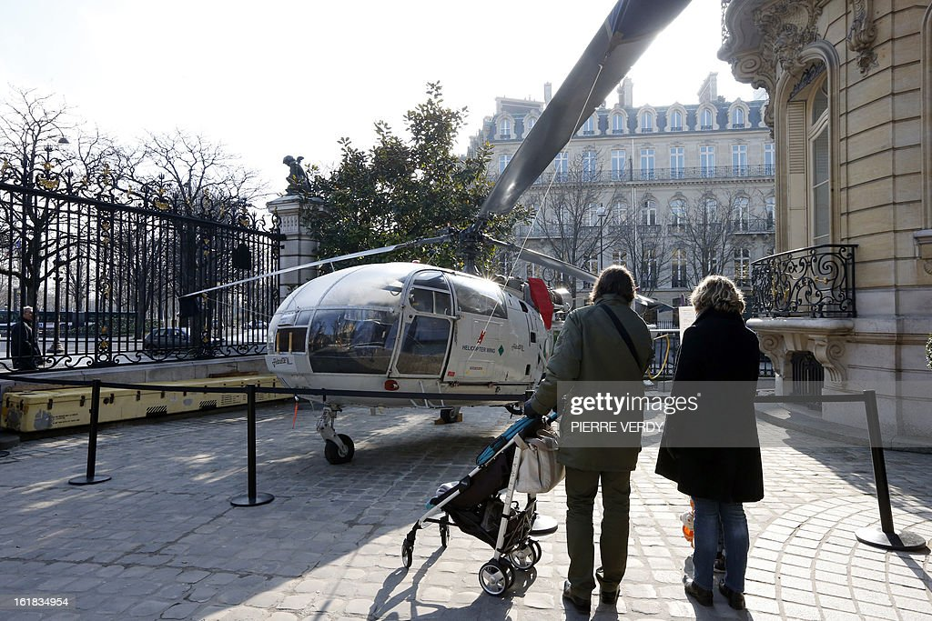 People look at an Alouette III helicopter displayed on February 17, 2013 in Paris in the courtyard of the Artcurial, French auction house, as part of the 'Aeronautics' auction sale. A 1959 De Havilland Vampire British jet fighter, whose value is estimated between 70,000 and 90 000 euros (USD), is the highlight of the auction of 500 lots.