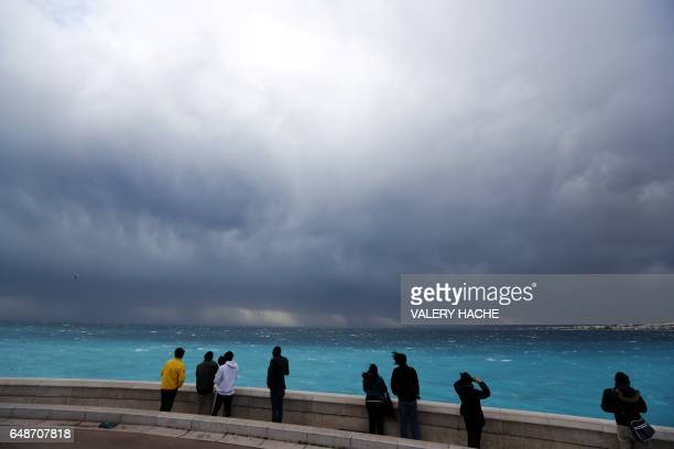 People look at an approaching storm on March 6 in Nice southeastern France / AFP PHOTO / VALERY HACHE