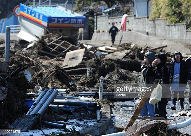 People look at an area flooded by the tsunami on March 12 2011 in Minamisoma Fukushima Japan An earthquake measuring 89 on the Richter scale hit the...
