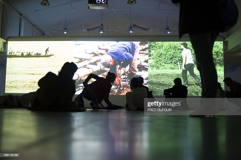 People look at an art installation by artist Phill Niblock 'The movement of people working', on October 4, 2013, in Paris, on the eve of Paris' Nuit Blanche (White Night) event. AFP PHOTO / FRED DUFOUR