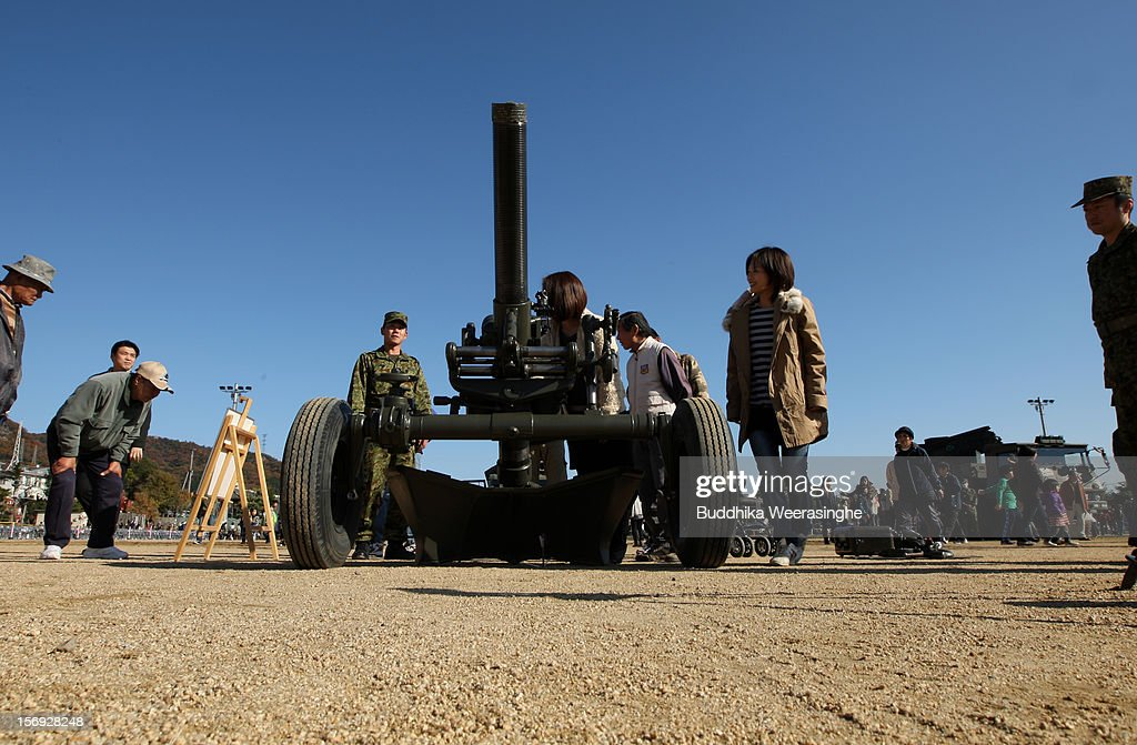People look at an artillery gun during the annual Japan Ground Self-Defense Force (JGSDF) military demonstration on November 25, 2012 in Himeji, Japan. The military exhibition and demonstration marks the 61-year anniversary of the Japan Ground Self-Defense Force based in Himeji.