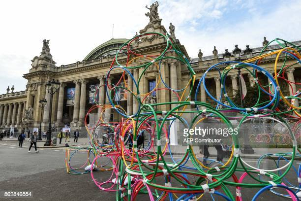 People look at an artwork untitled 'Hula hoops dimensions variable' by Hungarian artist Yona Friedman as they visit the Paris International...