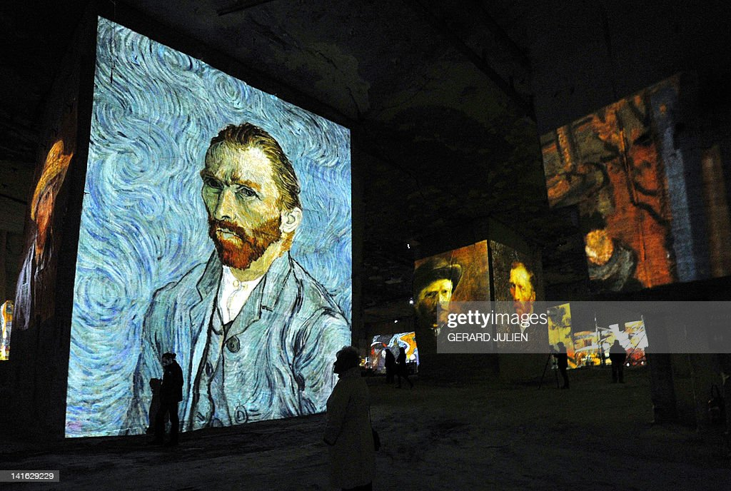 People look at an audio visual show projecting on the walls of the 'Carrieres de Lumieres' (Quarries of lights) paintings of French Post-Impressionist artist Paul Gauguin and Dutch post-Impressionist painter Vincent van Gogh, on March 20, 2012, in the southern French city of Les Baux de Provence.