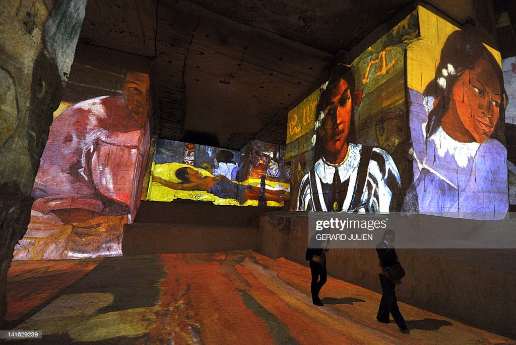 People look at an audio visual show projecting on the walls of the 'Carrieres de Lumieres' site (Quarries of lights) paintings of French Post-Impressionist artist Paul Gauguin and Dutch post-Impressionist painter Vincent van Gogh, on March 20, 2012, in the southern French city of Les Baux de Provence.