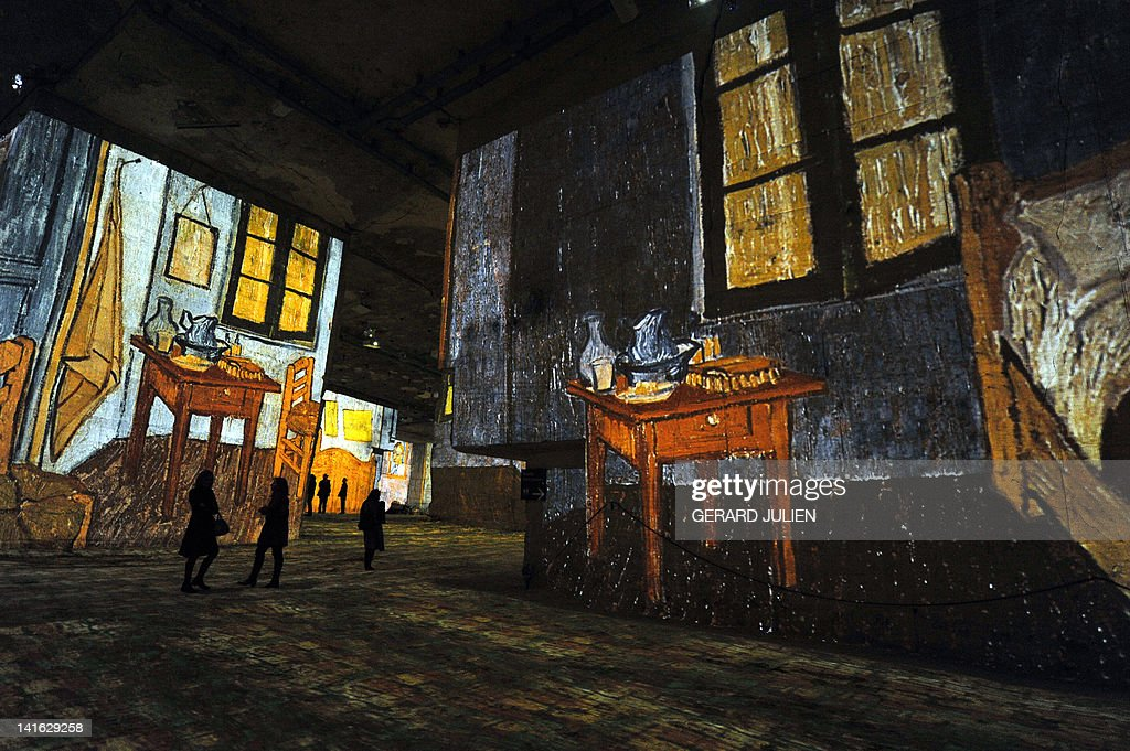 People look at an audio visual show projecting on the walls of the 'Carrieres de Lumieres' (Quarries of lights) paintings of French Post-Impressionist artist Paul Gauguin and Dutch post-Impressionist painter Vincent van Gogh, on March 20, 2012, in the southern French city of Les Baux de Provence. AFP PHOTO / GERARD JULIEN