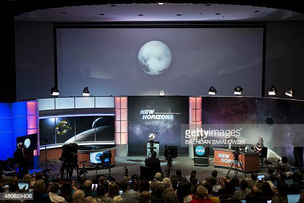 People look at an early image of Pluto taken by NASA's New Horizons probe as the craft makes its closest flyby of the dwarf planet at the Johns...