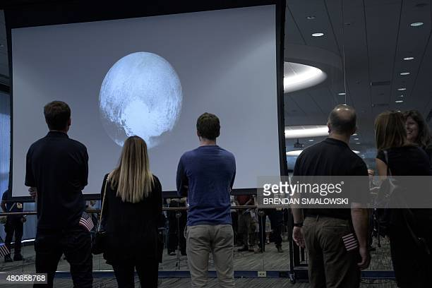 People look at an early image of Pluto taken by the New Horizons probe as the craft makes its closest flyby of the dwarf planet at the Johns Hopkins...