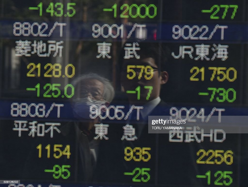 People look at an electric quotation board flashing share prices of the Tokyo Stock Exchange (TSE) in front of a securities company in Tokyo on February 9, 2016. Tokyo shares tumbled nearly five percent, extending a global sell-off as a stronger yen dented exporters and after oil prices tanked again on fears of a deepening economic slowdown. AFP PHOTO/Toru YAMANAKA / AFP / TORU YAMANAKA